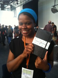 Veronica Louis holding a WordPress 10th Anniversary Notebook