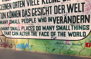 Photo of Berlin Wall that says small people in small places do many small things that can alter the face of the world