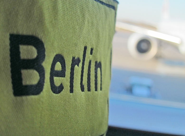 Small yellow purse with Berlin written on it with an airplane in the background
